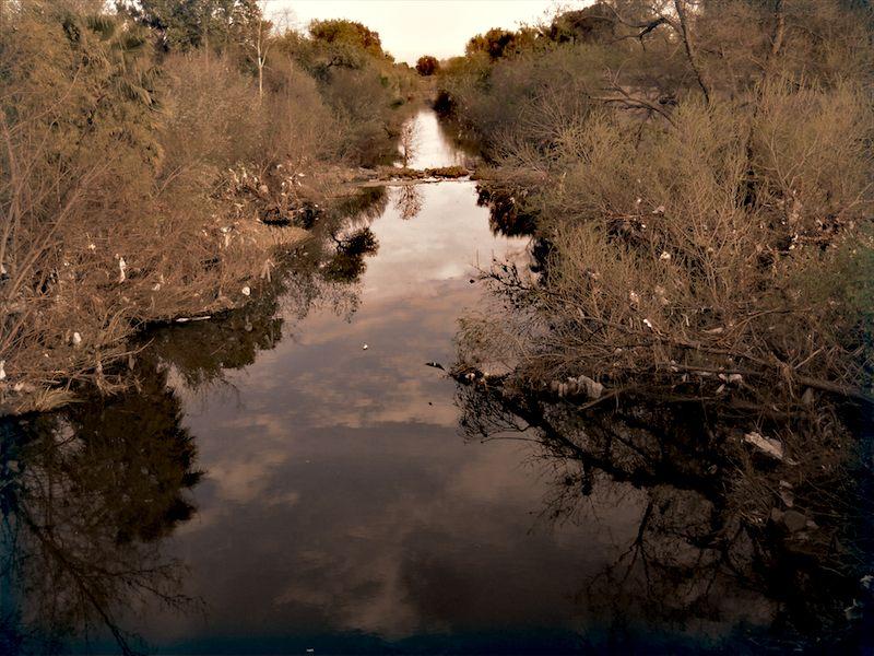Plastic bagged riparian banks, placid once again